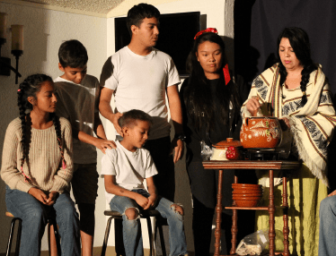 Marie Cobian, bottom, performs with Camacho's fictional family on stage. PHOTO BY ORLANDO JOSE