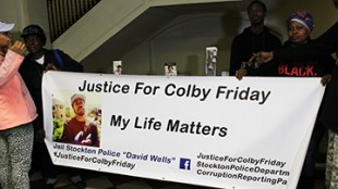 Denise Friday, left, and Deon Smith Downs, right, hold up a sign for Colby Friday at the April 7 Stockton City Council meeting. PHOTO BY MIKAEL HONZELL