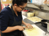 Social Media Editor, Evelyn Villalobos, cuts into chicken breast to prepare a food order. PHOTO BY FRANCINA SANCHEZ