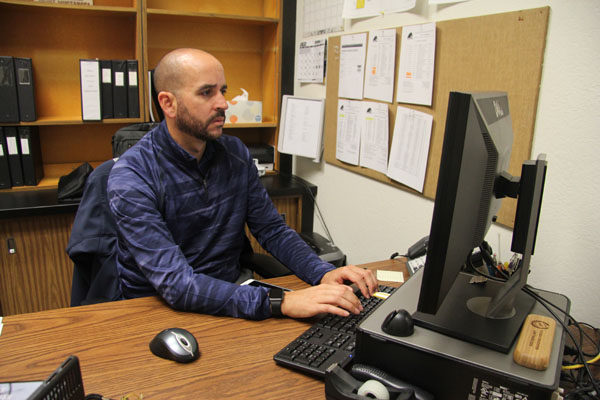 New athletic director Tony Espinoza at his desk in his office in the Budd center.