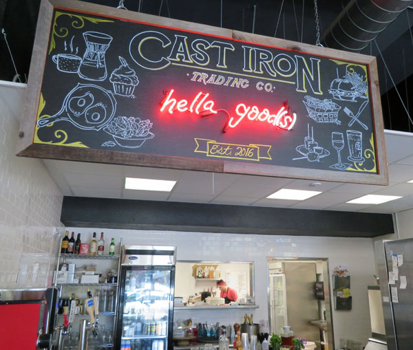 Cast Iron signs above counter welcomes customers.