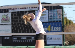 Ashley Apel hits the ball over the net during a beach volleyball practice.