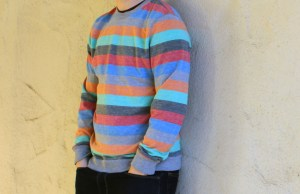 Student Noah Erickson showing off his garage sale find, a colorful striped sweater.