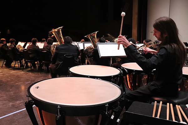 """Robin Bisho plays percussion behind all of the Symphonic Band during """"A Zillion Nickles"""" by Samuel Hazo, the opening song for Delta on 6 March 2019 in Atherton Auditorium. Photo by Vivienne Aguilar."""