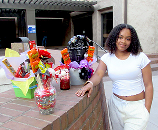 Second-year Delta College student Daja Cotton poses with gift baskets she made to sell. Photo by Hannah Workman.