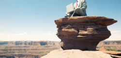 Traveling businessman sitting typing on his laptop looking out over massive rock canyon thinking about his employee benefits.