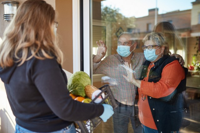 Senior couple wearing a protective face mask standing by the window indoors and watching a volunteer delivering a basket with groceries in times of COVID-19, she is wearing mask and gloves.