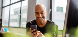 man smiling and using his cell phone for social media marketing at his work desk
