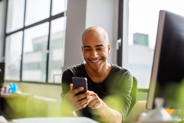 man smiling and using his cell phone to try social media marketing ideas at his work desk
