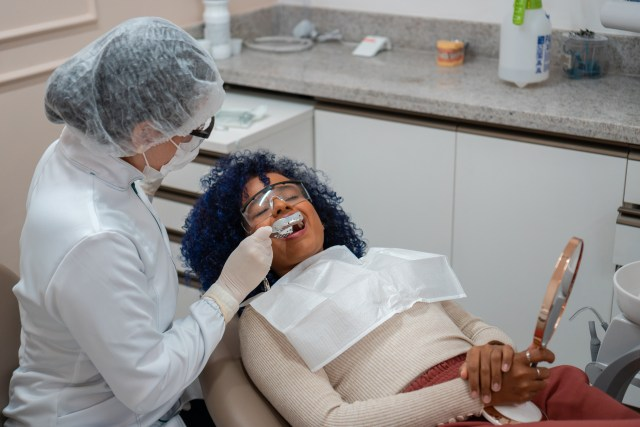 young woman having a mold taken of her mouth while visiting the dentist