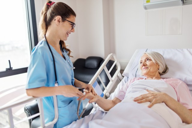 hospital nurse supports senior citizen and her oral health while making hospital rounds