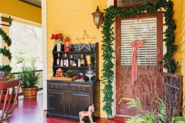 Keep your holiday decor traditional and vintage this year with front porch styling that's timeless, farmhouse-inspired and packed with old-school country charm. The front porch of the 2015 HGTV.com Holiday House is packed with classic country charm. Playing off of the mustard and barn red tones of the home's exterior, textural items packed with character and flea market appeal add a festive touch.