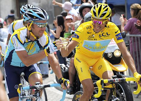 Astana rider Contador and team-mate Paulinho toast with champagne as they ride during the final 21th stage of the 96th Tour de France cycling race