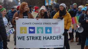 "Three teenagers holding sign: ""Climate Change Strikes Hard. We Strike Harder."