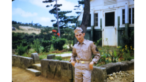 Soldier standing in front of house.