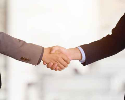 crop businessmen shaking hands in light office