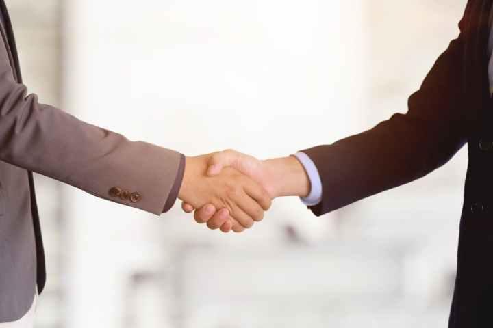 crop businessmen shaking hands in light office