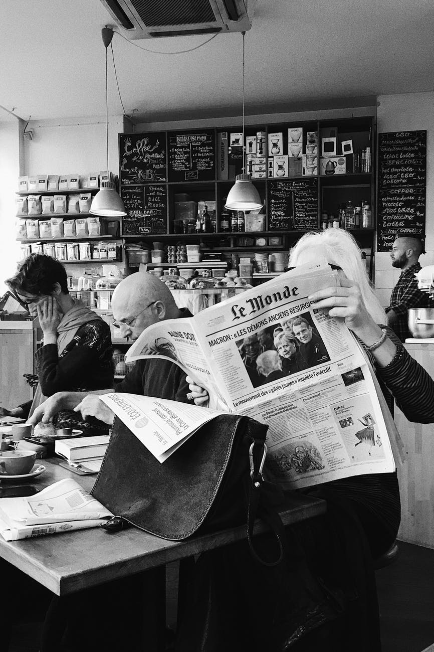 monochrome photo of woman holding newspaper
