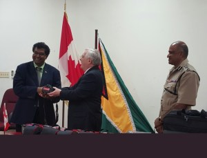 Canadian High Commissioner to Guyana Mr. Pierre Giroux hands over a piece of the equipment to Minister of Public Security Mr. Khemraj Ramjattan, while Commissioner of Police Mr. Seelall Persaud, DSM looks on appreciatively.