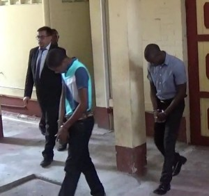 Immigration Officers Raduskie Wright (black shirt) and Orin Harris. At extreme left is Attorney-at-Law, Glen Hanoman.