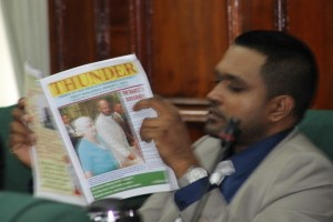 PPPC parliamentarian, Nigel Dharmlall reading a copy of his party's official organ, Thunder.
