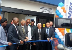 Minister of Business, Dominic Gaskin cutting the ribbon to declare the store open. Minister of Finance, Winston Jordan and Minister of Public Security, Khemraj Ramjattan also in picture.