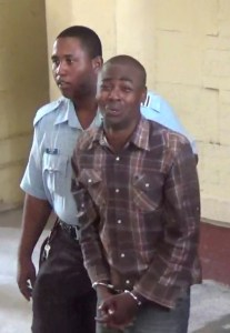 Samuel George being escorted by a policeman at the Georgetown Magistrates' Court.
