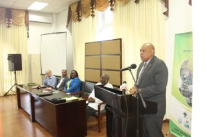 Minister of Natural Resources, Raphael Trotman addressing the opening of the EITI workshop. Seated are (from far left) Policy Forum Guyana's representative, Mike Mc Cormack; private sector representative, Hilbert Shields; Junior Natural Resources Minister, Simona Broomes and Chairman of the opening session, Ambassador Rudy Collins.