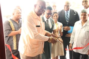Finance Minister, Winston Jordan cutting the ribbon to officially open the new office of the Ministry of Finance's Student Loan Agency.