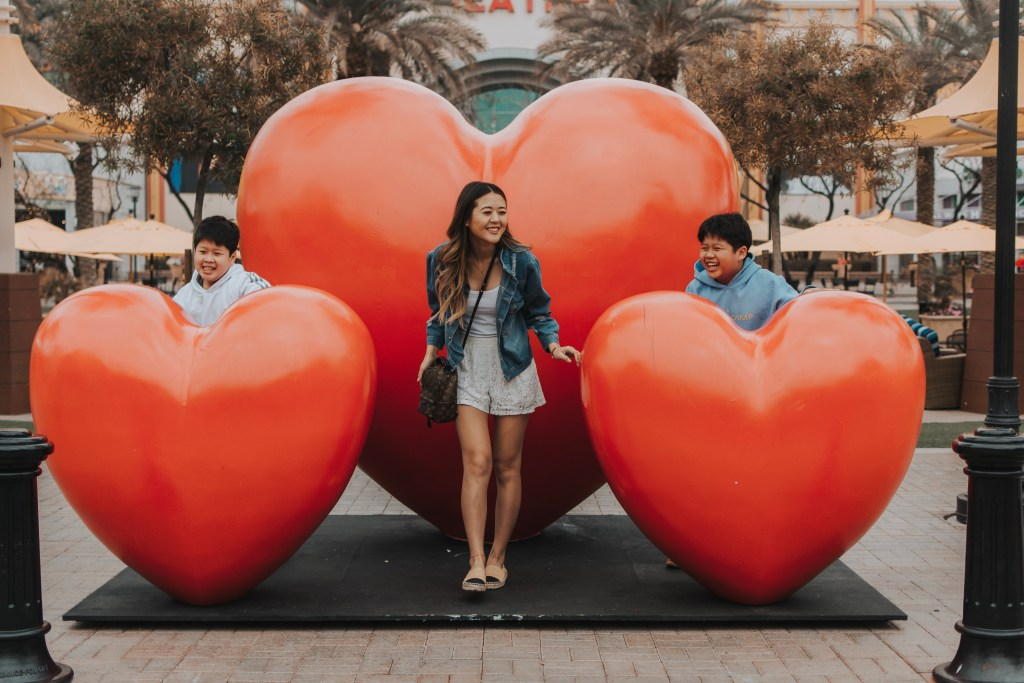 Arizona lifestyle blogger, Demi Bang, at Westgate Entertainment in front of their hearts pop-up art installation with her brothers.