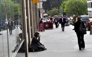 A beggar sitting on the pavementy looking for money. Picture by Bill Heaney