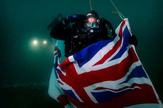 Royal Navy Divers, Northern Diving Group (NDG) flying and stowing a White Ensign on HMS Royal Oak for the 80th anniversary commemoration. 11.10.2019 in Scapa Flow, Orkney.
