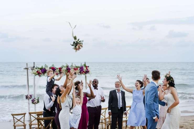 la mariée envoie son bouquet de fleur aux invités sur une plage.