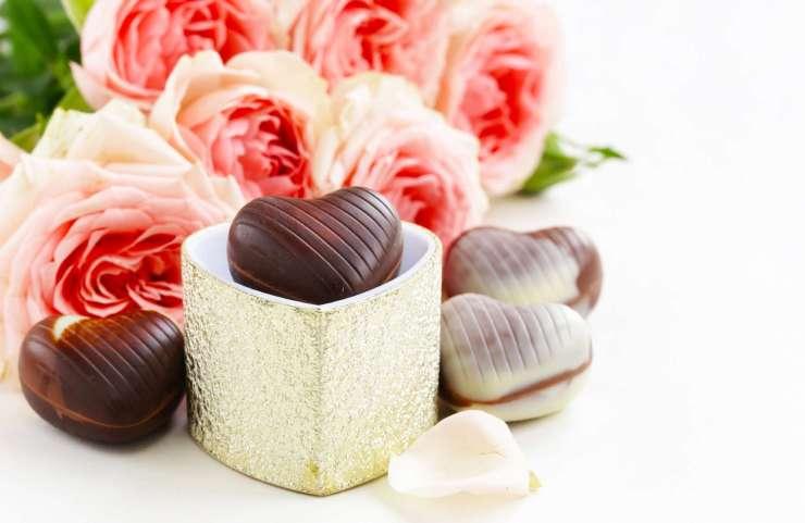 un chocolat se trouve dans une boite doré afin d'être offert aux invités. Il y a un bouquet de rose en arrière-plan