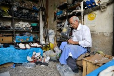 A man repairs shoes in a market.