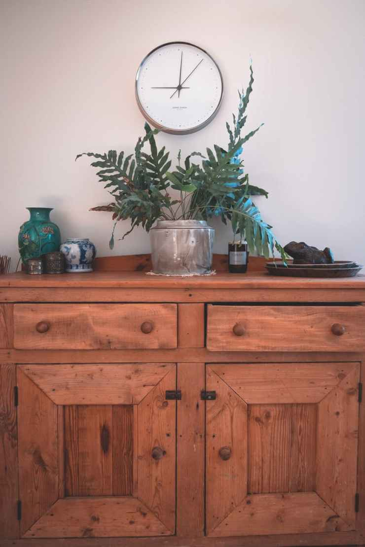round shaped clock hanging on wall above wooden cabinet