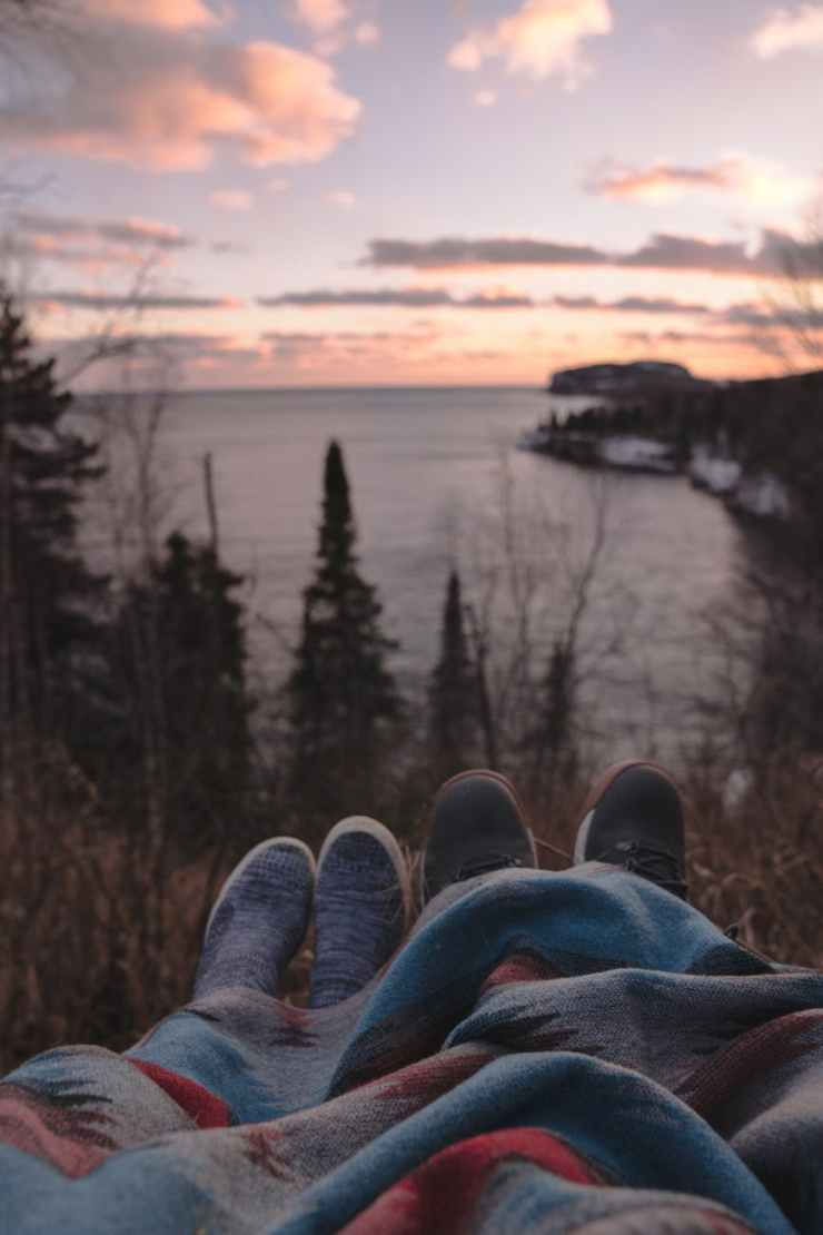 anonymous couple lying on hill at seaside and enjoying sunset time