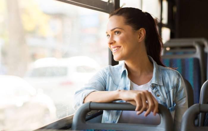 #ParaTodosVerem: Mulher sorrindo sentada em um ônibus de transporte público