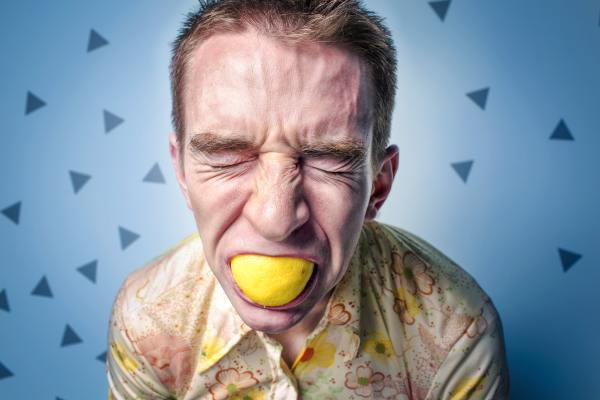 Man sucking on lemon causing tooth erosion
