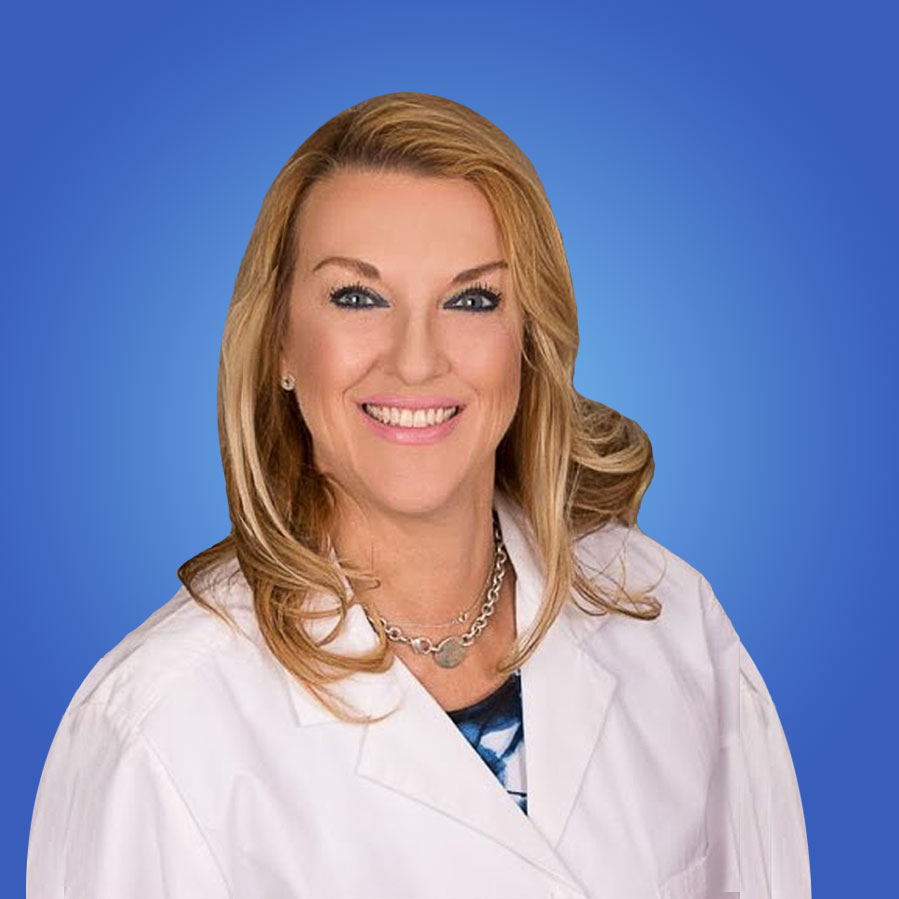 Aida Cappiello D.D.S. has sandy blond hair and is wearing a white lab coat