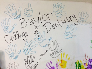 Outlines of volunteer hands cover the clinic walls.