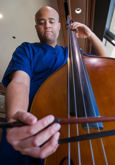 First-year dental student Talon Davis plays the double bass on the 17th floor of Roberts Hospital at Baylor University Medical Center