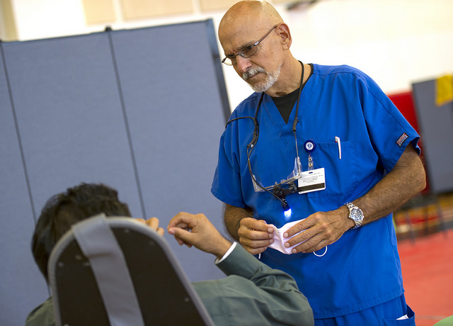 Dr. Lorenzo Prats, assistant professor of restorative sciences, consults with one of his first patients of the morning.
