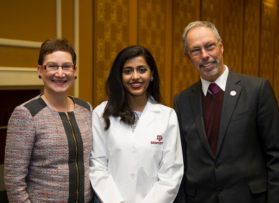 Dr. Carrie Byington and Dr. Lawrence Wolinsky pose for a photo with a student during the 2017 Texas A&M College of Dentistry White Coat Ceremony