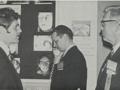 Dr. Roy Rinkle (left) and Dr. Kenneth Randolph (right) at the maxillofacial prosthetic center's exhibit during the Dallas Mid-Winter Clinic in 1971. Dr. Mack Charles Hughes (center), then a senior dental student, listens to one of the exhibit's tape recordings.