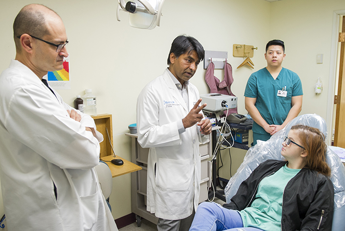 Dr. Likith Reddy, center, and Dr. Amirali Zandinejad, left, consult with Hannah McCain during an appointment at Texas A&M College of Dentistry in December 2017.