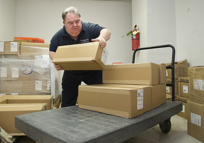 Marvin Vance loads a delivery cart in the college's storeroom.