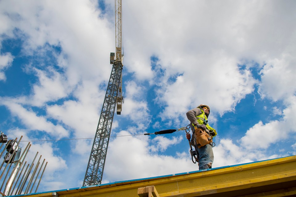 Construction worker pauses work above the second level of the new building in March 2018.