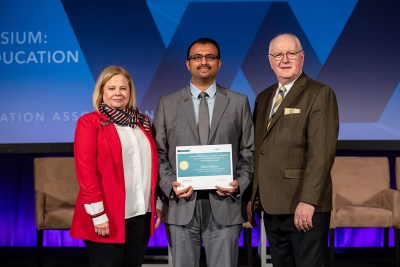 Dr. Faizan Kabani (center) accepts his award from Dr. R. Lamont MacNeil, the 2018-19 ADEA board chair (right), and Phyllis Martina with Colgate-Palmolive Co.