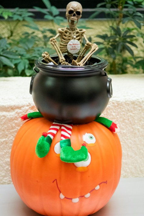 Pumpkin carved, with cauldron on top full of jello, and a skeleton